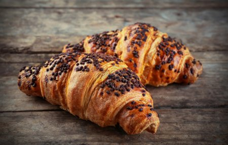 Photo for Fresh and tasty croissants with chocolate on wooden background - Royalty Free Image
