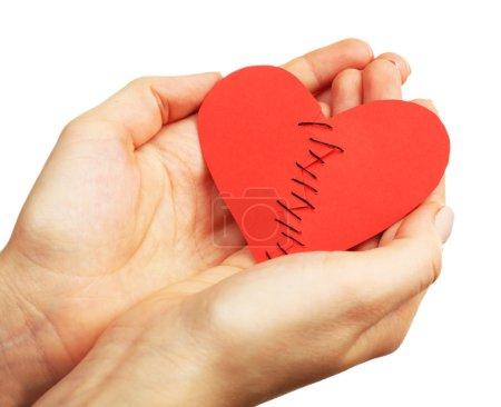 Photo pour Des mains féminines tenant coeur brisé cousu à deux pièces isolés sur blanc - image libre de droit