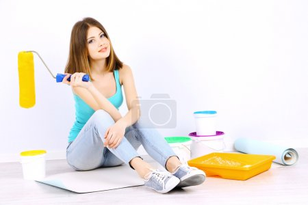 Beautiful girl sitting on floor with equipment for painting wall