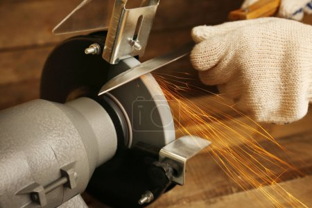 Photo for Knife sharpener and hand with blade on wooden table, closeup - Royalty Free Image