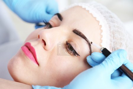 Cosmetologist applying permanent make up