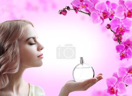 Photo pour Belle femme avec une bouteille de parfum de fleurs sur fond rose - image libre de droit