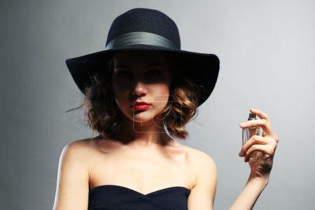 Photo pour Belle femme avec une bouteille de parfum sur fond gris - image libre de droit