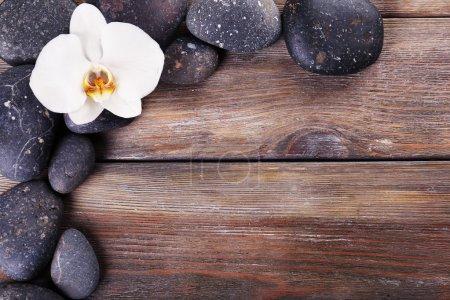 Photo pour Pierres de spa et fleur d'orchidée sur fond en bois - image libre de droit
