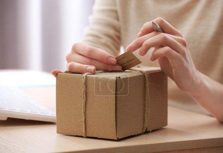 Woman signs parcel in post office