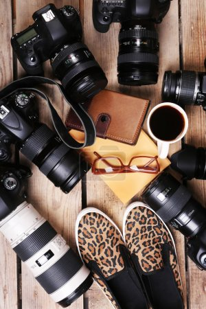 Still life with modern cameras on wooden table, top view