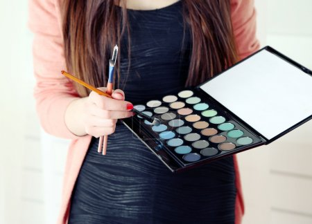 Female makeup artist with cosmetics