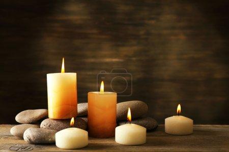 Photo pour Belle composition avec bougies et pierres de spa sur fond en bois - image libre de droit