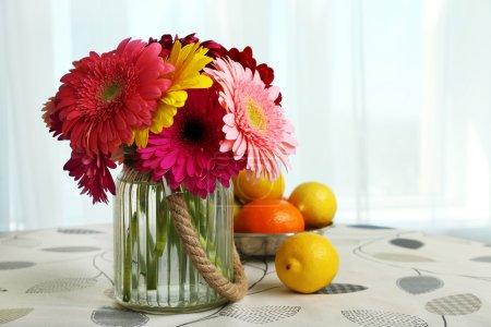 Photo pour Fleurs de gerbera colorées dans un vase en verre avec des fruits sur la table sur fond rideaux - image libre de droit