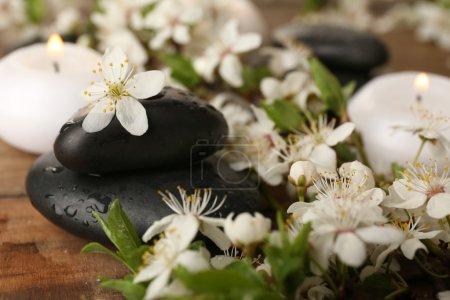 Foto de Piedras de spa con velas y flores de primavera en la mesa de cierre - Imagen libre de derechos