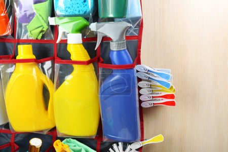 Household chemicals in holder hanging on wooden door, closeup