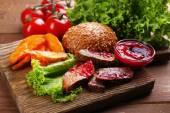 Rindfleisch mit Cranberry-Sauce, gebratene Kartoffel-Scheiben und Brötchen auf Schneidebrett auf hölzernen Hintergrund
