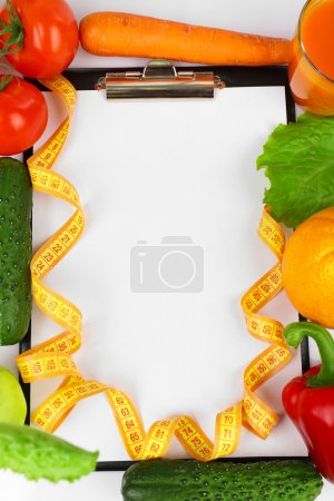 Clipboard for diet plan with vegetables and measuring tape, closeup