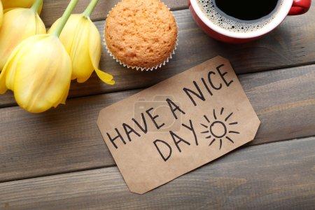 Photo pour Tasse de café avec cupcake frais, tulipes et avoir une belle journée massage sur fond de bois - image libre de droit