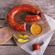 Smoked sausage on cutting board on wooden table ba...