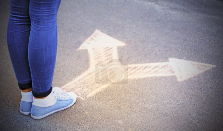 Photo for Female feet and drawing arrows on pavement background - Royalty Free Image