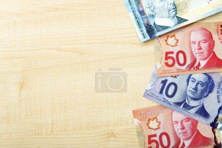 Photo pour Dollars canadiens sur table en bois - image libre de droit