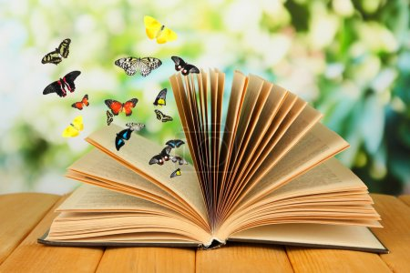 Open book on wooden table and butterflies