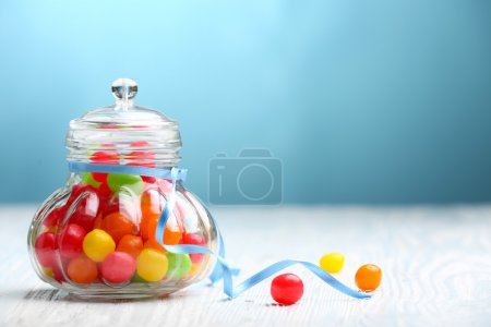 Photo for Colorful candies in jar on table on blue background - Royalty Free Image