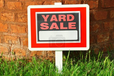 Wooden Yard Sale sign in green grass on red brick wall background