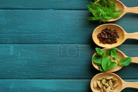 Wooden spoons with fresh herbs and spices on color wooden background