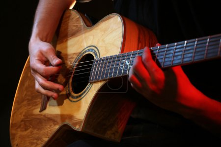 Photo for Young man playing on acoustic guitar close up - Royalty Free Image