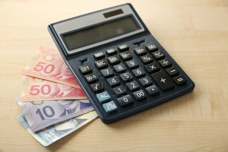 Photo pour Calculatrice et dollars canadiens, sur table en bois - image libre de droit