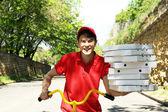 Mladý muž, dodávající pizza box na kole venku