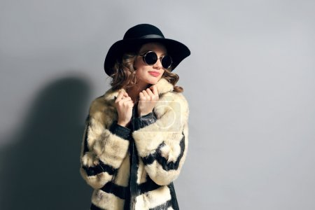 Portrait of beautiful model in fur coat, hat and sunglasses on gray background
