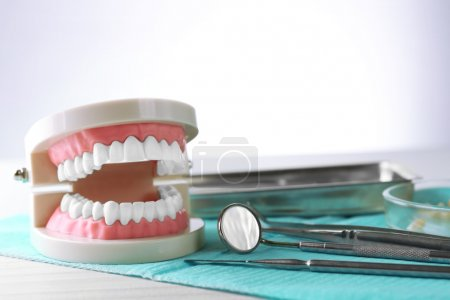 White teeth and dental instruments on table backgr...