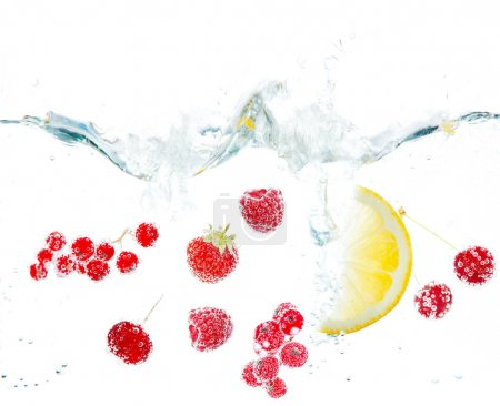 Fresh fruits and berries splashing in water isolated on white