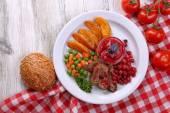 Hovězí maso s brusinkovou omáčkou, opečené bramborové plátky, zeleninou a buchta na desku, na barevné dřevěné pozadí