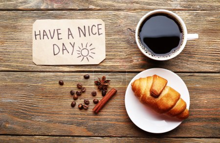 Cup of coffee with fresh croissant and Have A Nice Day massage on wooden table, top view