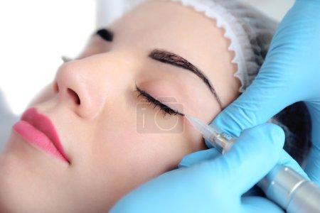 Photo pour Cosmetologue appliquant un maquillage permanent sur les yeux, gros plan - image libre de droit
