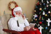 Santa Claus sitting with Digital tablet in comfortable chair near Christmas tree at home