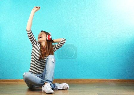 Photo pour Jeune femme assise sur le sol avec un casque sur fond turquoise - image libre de droit
