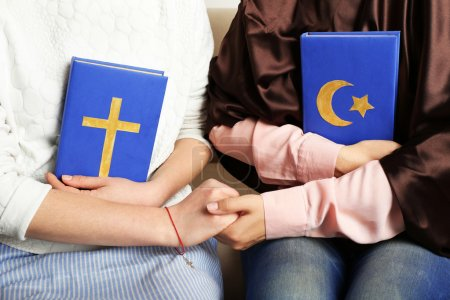 Photo for Two friends holding books with religions symbols - Royalty Free Image