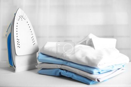 Photo for Pile of clothes and electric iron on fabric background - Royalty Free Image