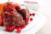 ízletes sült hús, sült zöldség a tányéron, a világos háttér és vörösáfonya szósszal