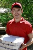 Szállítási fiú karton pizza doboz ház közelében ügyfél, szabadban