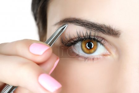 Photo for Young woman plucking eyebrows with tweezers close up - Royalty Free Image