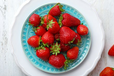 Ripe strawberries in plate, top view