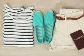 Letní dovolená oblečení, boty a klobouk na dřevěné pozadí