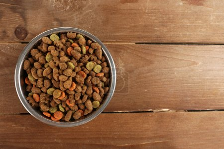 Dog food in bowl on wooden table...