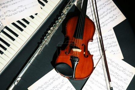 Photo pour Instruments de musique avec des notes de musique sur fond foncé - image libre de droit