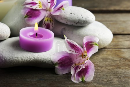 Photo pour Spa nature morte avec fleurs violettes, les cailloux et les bougies sur table en bois, gros plan - image libre de droit