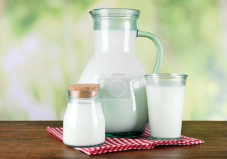 Pitcher, jar and glass of milk on wooden table, on nature background