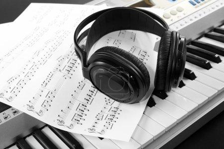 Photo pour Écouteurs avec notes de musique sur synthétiseur close up - image libre de droit