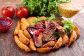 Rindfleisch mit Cranberry-Sauce, gebratene Kartoffel-Scheiben und Brötchen auf Holz schneiden Brett, close-up