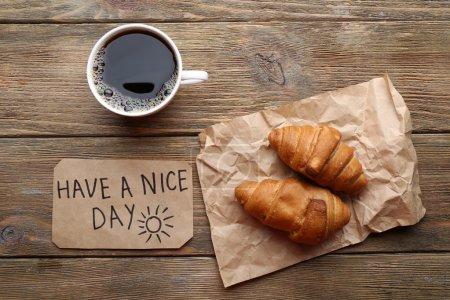 Photo pour Tasse de café avec croissant frais et avoir une belle journée de massage sur une table en bois, vue sur le dessus - image libre de droit